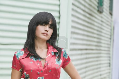 Hispanic woman standing in front of aluminum siding