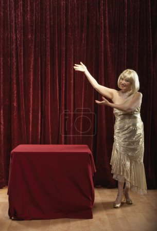 Woman on stage in gown with arms posed