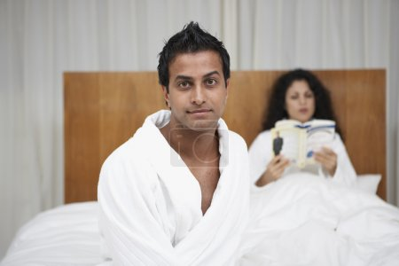 Middle Eastern man in bathrobe with woman reading in bed