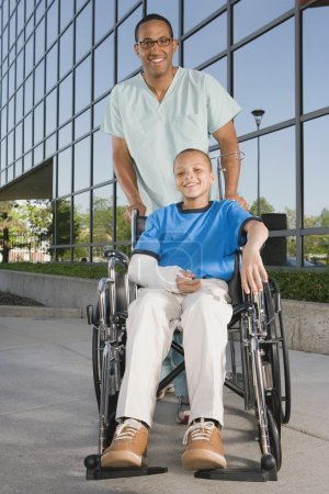 African boy in wheelchair with nurse in front of hospital