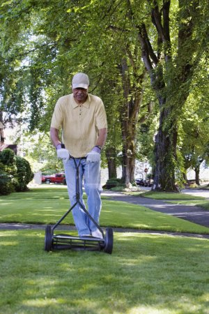 Middle-aged man mowing the lawn