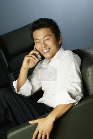 Young Asian businessman using cell phone in armchair