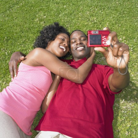 African couple laying on grass and taking own photograph