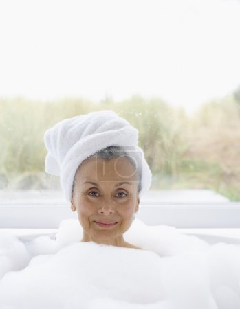 Elderly woman in bubble bath with towel wrapped around head