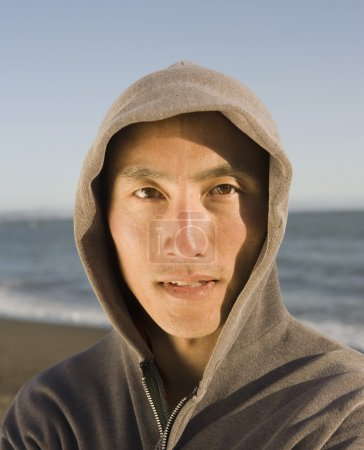 Asian man wearing hooded sweatshirt