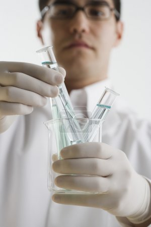 Scientist examining chemicals in test tubes