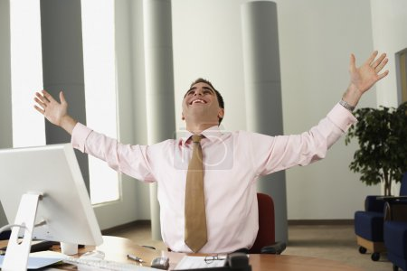 Middle Eastern businessman cheering at desk