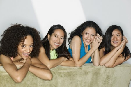 Group of young women lying on a bed looking at camera smiling