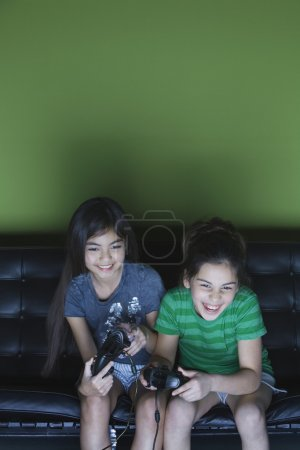 Two girls playing video game on sofa