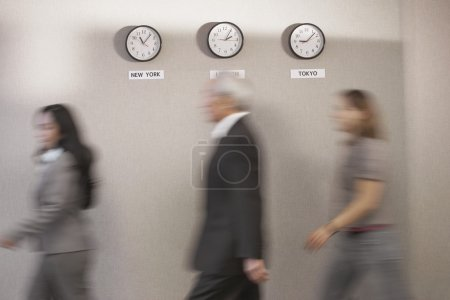 Business people walking past world time zone clocks