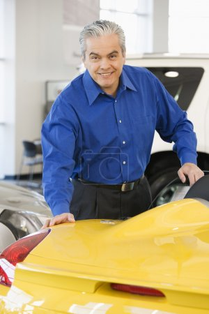 Hispanic car salesman looking at new car