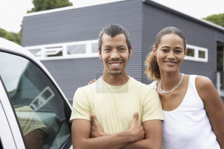 Multi-ethnic couple standing next to car