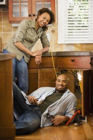 African couple installing kitchen sink