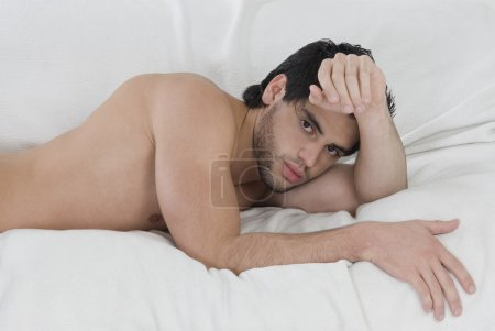 Bare-chested Hispanic man laying on bed