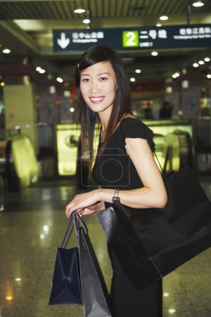 Asian woman carrying shopping bags in subway
