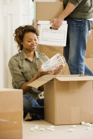 African couple unpacking in new house