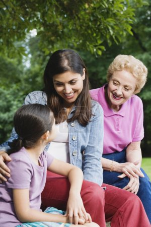 Hispanic grandmother, mother and daughter sitting together