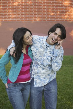 Young Hispanic couple using cell phone outdoors