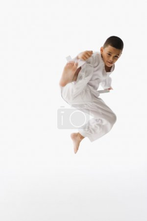 Hispanic boy performing martial arts kick