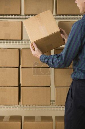 Mature man stacking cardboard boxes
