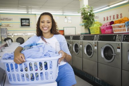 Woman with basket of clothes in laundromat