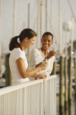 Two women drinking wine on marina balcony