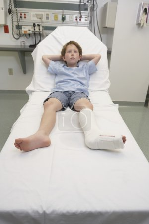 Young boy with broken leg laying in hospital bed