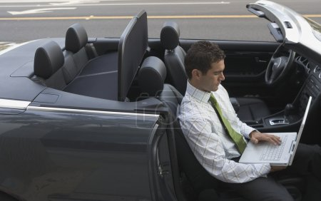 Businessman working on laptop while sitting in convertible