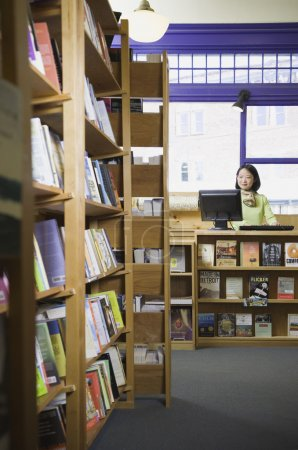 Asian female saleswoman at bookstore