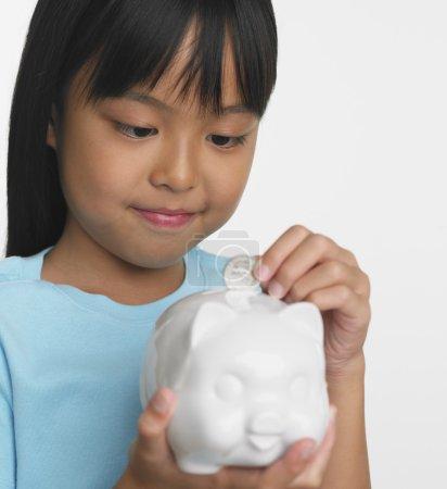Young Asian girl putting coin in piggybank