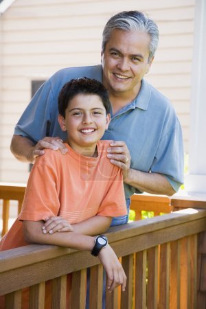 Hispanic father and son smiling on porch