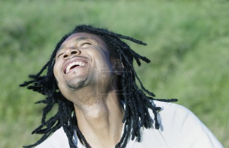 Man sitting outdoors looking up smiling