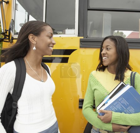 Two young African women next to school bus talking