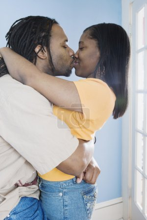 Young African couple hugging and kissing
