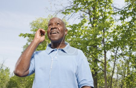 Senior African man with mp3 player outdoors