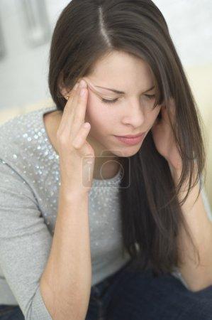Hispanic woman rubbing head