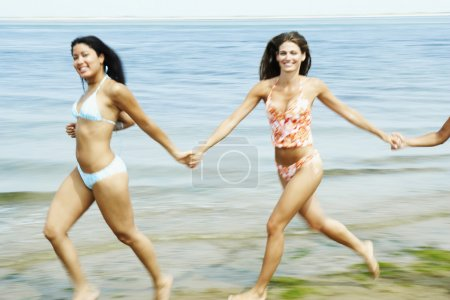 Women holding hands and running at beach