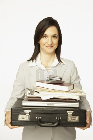 Hispanic woman carrying briefcase piled with work