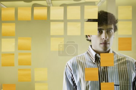 Businessman standing behind decorative glass