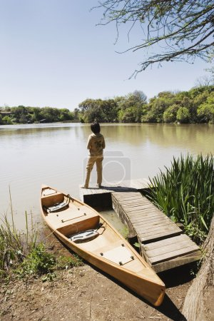 Woman standing on dock next to canoe