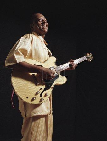 Senior man playing guitar joyfully