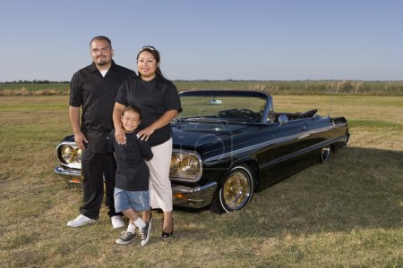 Hispanic family in front of low rider car