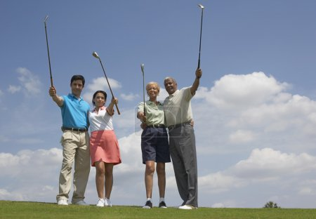 Multi-ethnic couples holding golf clubs