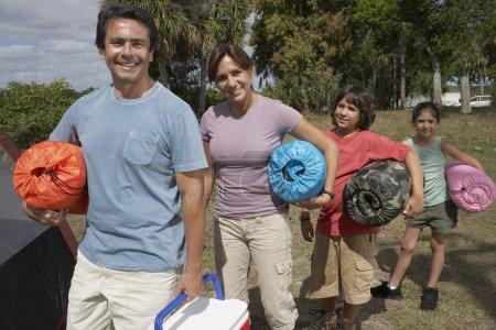 Hispanic family holding sleeping bags