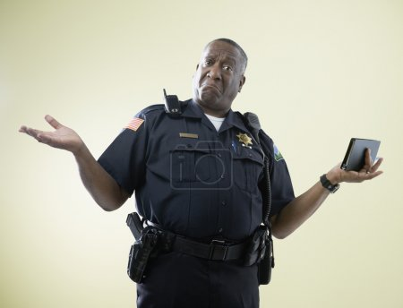 African American male police officer shrugging shoulders