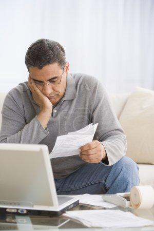Hispanic man paying bills