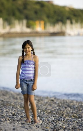 Mixed Race girl standing on rocky beach