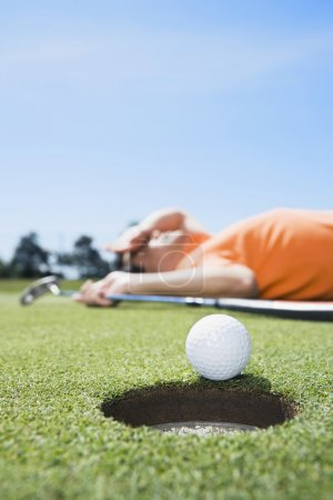 Golfer laying on ground next to golf ball on edge of hole