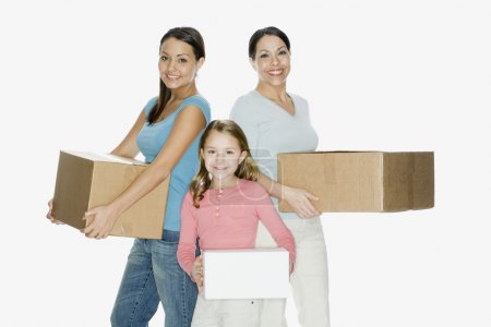 Hispanic mother and daughters holding moving boxes