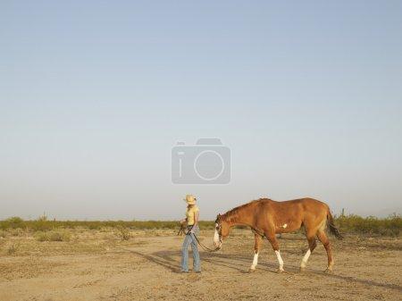 Hispanic woman leading horse